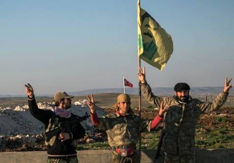 yrian Kurdish militia members of the YPG make a V-sign next to a drawing of Abdullah Ocalan, jailed Kurdish rebel leader, in Esme village in Aleppo province, Syria.