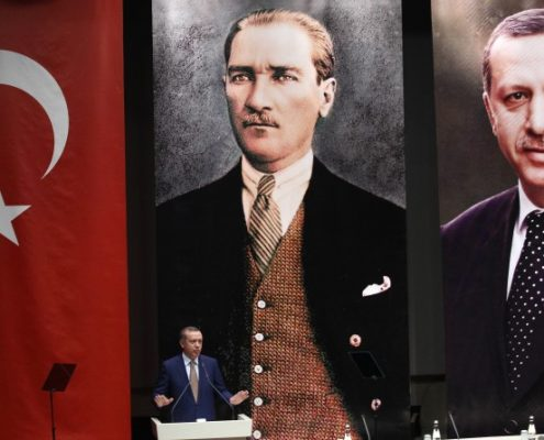 Turkey's Prime Minister Recep Tayyip Erdogan addresses members of his ruling AK Party, as he stands in front of portraits of himself (R) and Mustafa Kemal Ataturk, the founder of modern Turkey, during a meeting at his party headquarters in Ankara on May 23, 2014. AFP PHOTO / ADEM ALTAN        (Photo credit should read ADEM ALTAN/AFP/Getty Images)